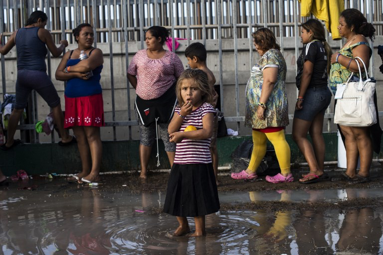 Child standing in water waiting at the US/Mexico Border